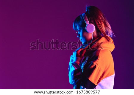 Happy igen teen hipster fashion girl model wear stylish glasses headphones enjoy listen new cool trance music mix stand at purple studio background in trendy 80s 90s club party light, profile view