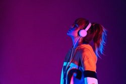 Happy igen teen hipster pretty fashion girl model wear stylish glasses headphones enjoy listen new cool music mix stand at purple studio background in trendy 80s 90s club party light, profile view