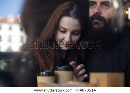 Happy, in love couple, of two hipsters, young woman and middle aged bearded man, cuddle and hug in cafe window. Drink coffee from take away cups and show affection and tenderness #794073514
