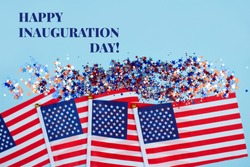 Happy Inauguration Day - creative composition with USA flags on blue background, copyspace for text. Inauguration Day 2021 concept. Selective focus