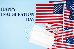 Happy Inauguration Day - creative composition with USA flags on blue background, hand sanitizer and disposable face masks, copy space for text. Inauguration Day 2021 concept. Selective focus