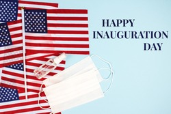Happy Inauguration Day - creative composition with USA flags on blue background, sanitizer and disposable face masks, copy space for text. Inauguration Day 2021 concept. Selective focus