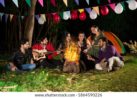 Happy Indian asian friends playing music and enjoying bonfire or campfire in nature