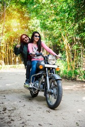 Happy Indian asian happy young woman or female friends riding on motorcycle or motorbike on the forest road