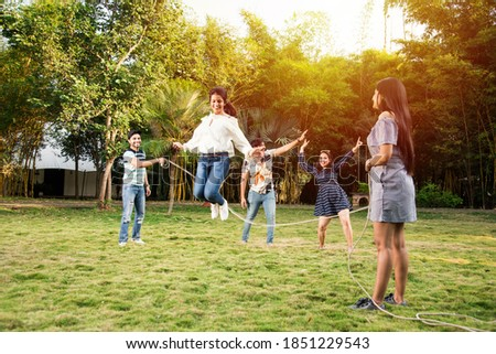 Happy Indian asian young friends playing together with jumping rope outdoors. People playing skipping rope games and laughing outdoors. Happy man or woman jumping over skipping rope held by others