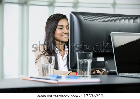 Happy Indian business woman at office desk working on a computer
