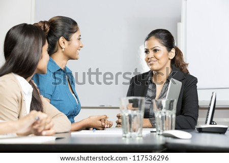 Happy Indian business woman sitting with her colleagues in a meeting - stock photo