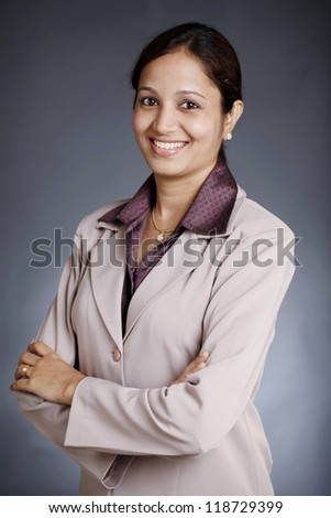Happy Indian Business woman with arms crossed on grey background