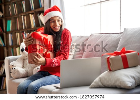 Happy indian child kid girl wearing santa hat holding Christmas gift box, showing New Year present to webcam talking with family, social distance friend by video conference call meeting chat at home.