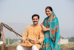 Happy Indian couple in traditional clothing at village