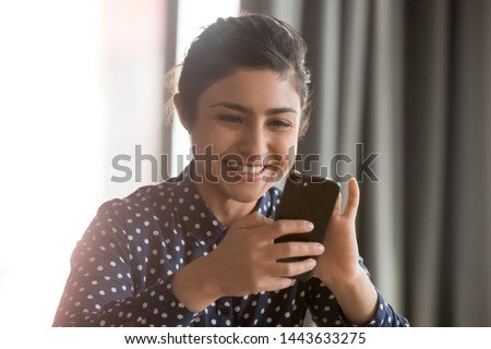 Happy indian ethnic business woman using smartphone at home office, smiling hindu girl having fun with cell phone texting sms play mobile games using apps for business or entertainment concept