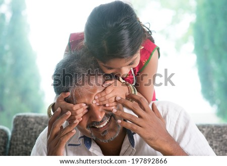 Happy Indian family at home. Asian girl surprising her father by covering daddy eyes. Parent and child indoor lifestyle.