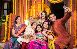 Happy Indian Family Celebrating Ganesh Festival or Chaturthi - Welcoming or performing Pooja and eating sweets in traditional wear or taking selfie picture at home decorated with Marigold Flowers