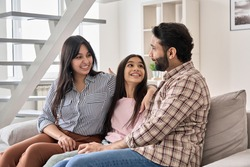Happy indian family couple with teen child daughter bonding, hugging, talking sitting on couch at home. Smiling husband and wife embracing child spending time together relaxing on sofa in living room