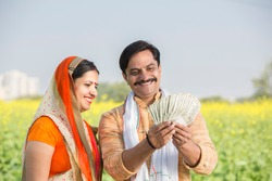 Happy Indian farmer with wife holding Indian rupee notes in agriculture field