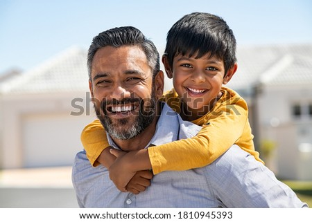 Happy indian father giving piggyback ride to his son and looking at camera. Cute ethnic boy with dad playing outdoor. Close up face of handsome man carrying on shoulders his middle eastern kid.