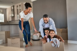 Happy indian father playing with daughters sitting in carton box. Happy multiethnic family having fun together in new house. Smiling dad pushing excited little girls in cardboard box after relocation.