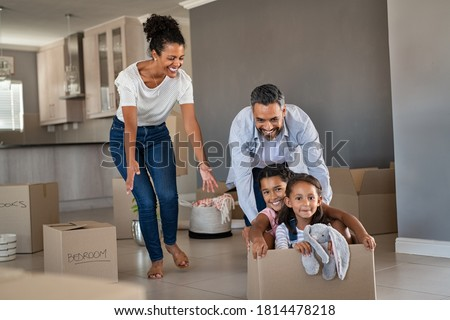 Happy indian father playing with daughters sitting in carton box. Happy multiethnic family having fun together in new house. Smiling dad pushing excited little girls in cardboard box after relocation. Сток-фото ©