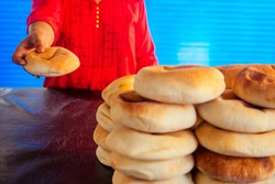 happy indian female salling fresh traditional buns in bazar