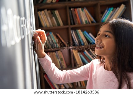 Happy indian kid primary school girl pupil holding chalk writing on blackboard. Smiling latin child preteen schoolgirl learning english alphabet letter handwriting standing in classroom. Close up view