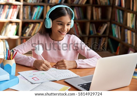 Happy indian latin preteen girl school pupil wearing headphones distance learning online at virtual class with teacher tutor on laptop by video conference call, watching tv lesson at home.