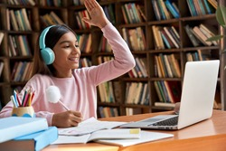 Happy indian latin preteen girl school pupil wearing headphones raising hand distance learning online at virtual lesson class with teacher tutor on laptop by zoom video conference call at home.