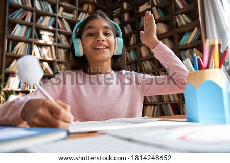 Happy indian latin preteen girl school pupil wearing headphones raising hand distance learning online at virtual lesson class with teacher tutor by video conference call at home, webcam view.