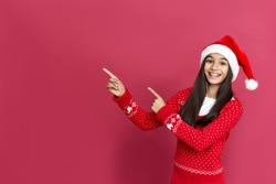 Happy indian latin preteen girl wearing santa hat pointing at copy space standing isolated on red background. Merry Christmas sale, parties for kids, children Happy 2021 New Year celebration concept.