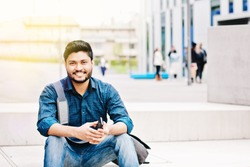 Happy indian male student holding smartphone sitting outdoor