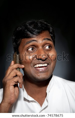 Happy Indian man talking on the cell phone at black background