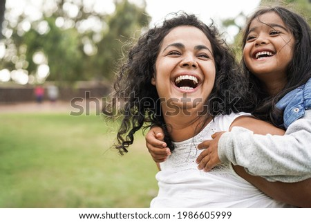 Happy indian mother having fun with her daughter outdoor - Family and love concept - Focus on mum face