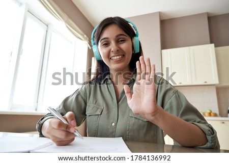 Happy indian online teacher, student ot tutor wearing headphones looking at webcam video conference calling in virtual chat application remote teaching giving online class school lesson. Headshot.