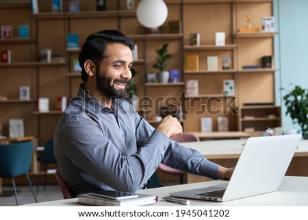 Happy indian professional young adult man having video conference call virtual business meeting working on laptop computer, enjoying watching online webinar, seminar training or remote class concept.