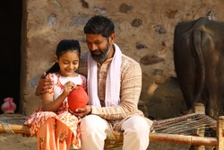 Happy Indian rural family of father and daughter sitting on a folding bed in outdoors holding a piggy bank. Father teaching his daughter the benefits of saving money.
