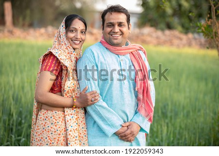 Happy indian rural farmer couple in agricultural field. Stockfoto ©