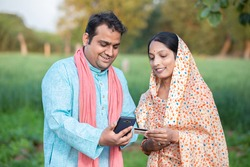 Happy indian rural farmer couple using smartphone to make online payment with debit card in agricultural field, shopping on internet with cellphone secure banking service system concept.