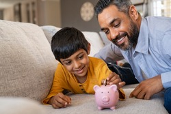 Happy indian son saving money in piggy bank with father. Lovely ethnic father teaching to little boy importance of saving money for future. Smiling middle eastern kid adding coin in piggybank with dad