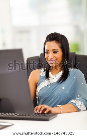 happy indian woman in traditional clothing using computer at work
