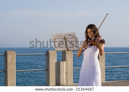 happy indian woman play violin on beach pier
