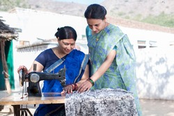 Happy Indian woman sewing clothes with sewing machine