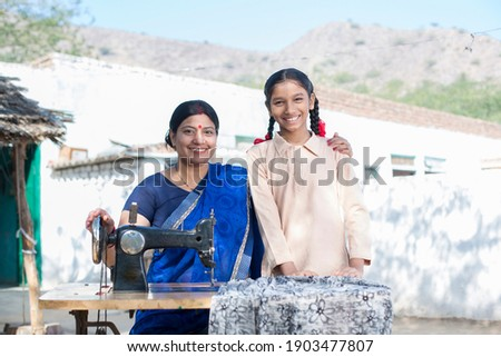 Happy Indian woman sewing clothes with sewing machine with daughter. Stock photo ©