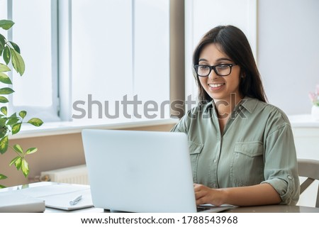 Happy indian young adult woman wearing glasses using pc laptop computer working studying at home office sitting at table. Happy female professional freelancer learning watching online webinar training