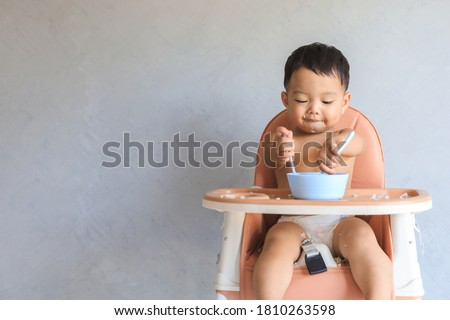 Happy infant Asian baby boy eating food by himself on baby high chair and making mess with copy space. Stock foto ©