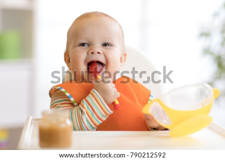 Happy infant baby boy spoon eats itself at home