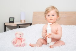 Happy Infant baby toddler sitting on parents bed after bath or shower, holding a bottle in the hand with shower gel, playing with cosmetic tubes. Clean dry child in bedroom. Children hygiene concept.