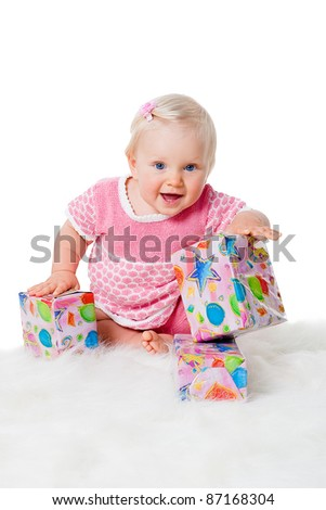 happy infant girl sitting with gift boxes on white background