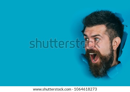 Happy, interested man looking through hole in paper wall. ?heerful bearded man making hole in blue paper. Surprised bearded male head looking through hole. Sale, discount, season sales. Copy space.