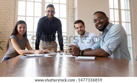 Happy international professional business people sit together at office table, smiling friendly diverse staff multiracial employees corporate workers group look at camera in boardroom, team portrait