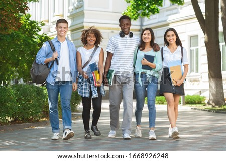 Happy Interracial College Friends Walking In Campus And Smiling To Camera, Enjoying Spending Time Together Outdoors, Free Space
