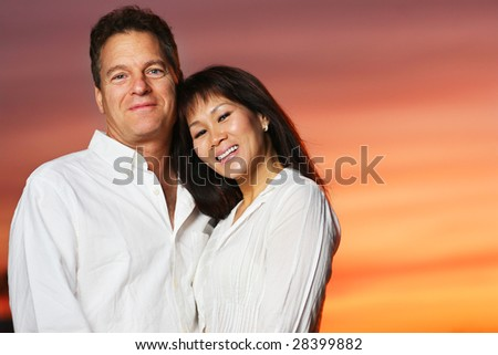 Happy interracial couple at sunset